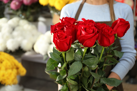 Saleswoman holding bouquet of beautiful roses in shop Stockfoto