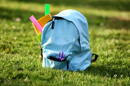 Color rucksack with school stationery on ground outdoors