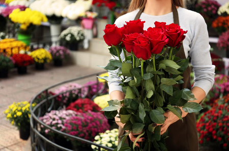 Saleswoman holding bouquet of beautiful roses in shop Stock fotó