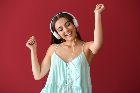 Beautiful woman listening to music on color background Banque d'images