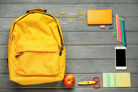 Composition with rucksack and school stationery on wooden background, top view