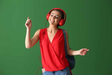 Beautiful woman listening to music on color background Standard-Bild