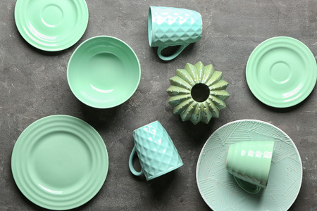 Tableware and decorative vase on grey background