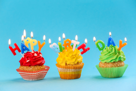 Tasty birthday cupcakes with candles on color background