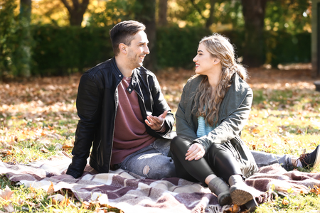 Loving young couple sitting on plaid in autumn park