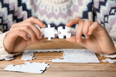 Woman doing puzzle at table, closeup 免版税图像