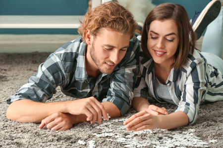 Young couple doing jigsaw puzzle at home