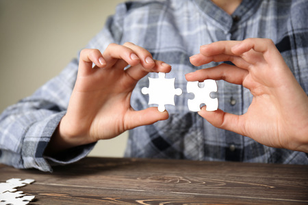 Woman with pieces of puzzle at table, closeup