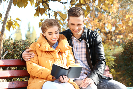 Loving young couple reading book in autumn park Imagens
