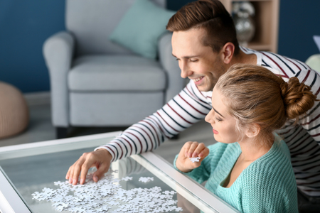 Young couple assembling puzzle on glass table at home