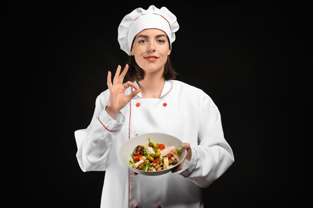 Young female chef with salad on dark background