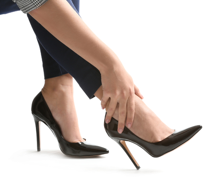 Young woman in high-heeled shoes suffering from leg pain on white background Banco de Imagens