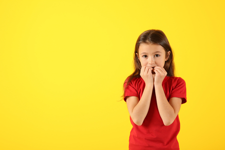 Emotional girl after making mistake on color background Archivio Fotografico