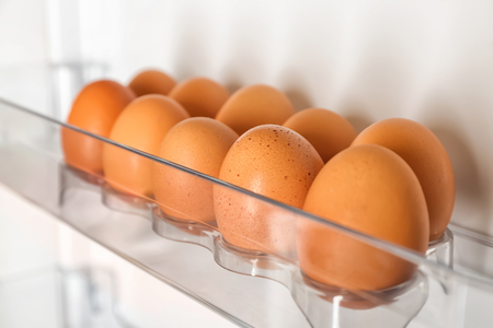 Raw chicken eggs in fridge, closeup