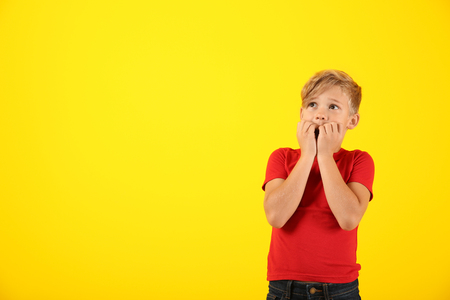 Emotional boy after making mistake on color background Stock Photo