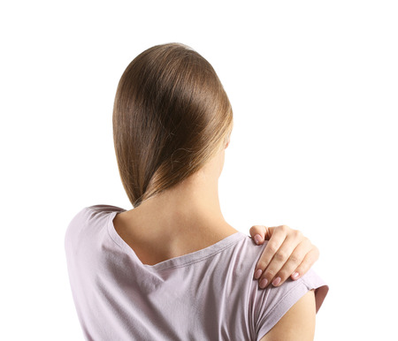 Young woman suffering from pain in shoulder on white background