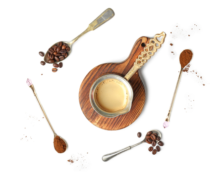 Jezve with hot coffee and spoons on white background 免版税图像