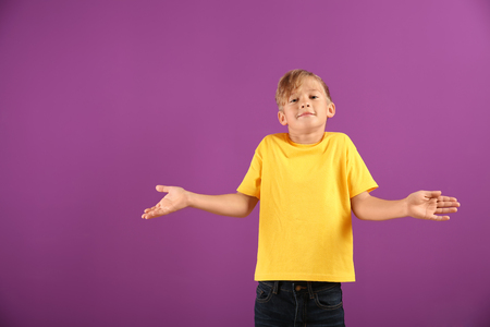 Emotional boy after making mistake on color background Фото со стока