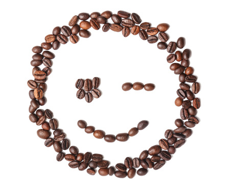 Funny smiling face made of roasted coffee beans on white background