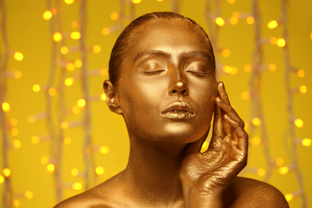 Beautiful young woman with golden paint on her body against defocused lights