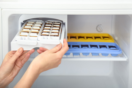 Woman taking trays with coffee ice cubes out of fridge 版權商用圖片