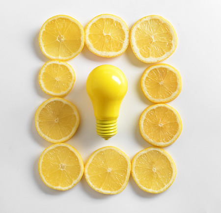 Painted light bulb with lemon slices on white background