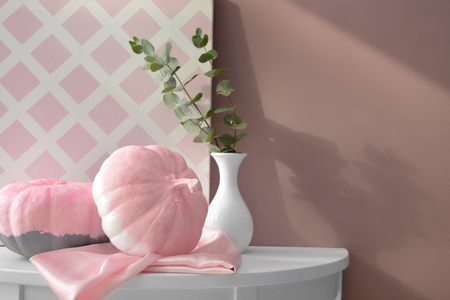Painted pumpkins with vase on white table in room