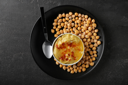 Bowl with tasty hummus and chickpeas on plate Stock Photo