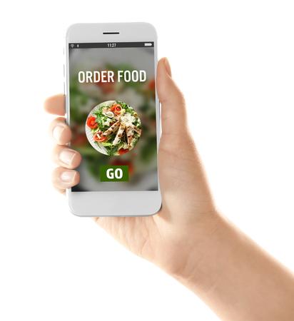 Vrouw met mobiele telefoon met open pagina van voedselbezorgservice op witte achtergrond Stockfoto