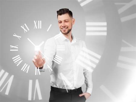 Businessman with virtual clock on grey background. Time management concept