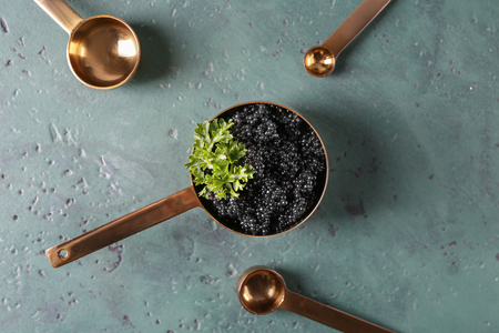 Scoop with delicious black caviar on color table