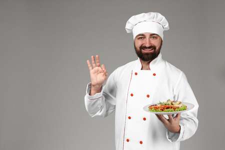 Male chef with tasty dish on grey background