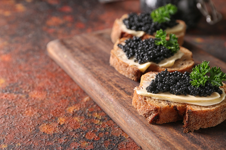Delicious sandwiches with black caviar on wooden board