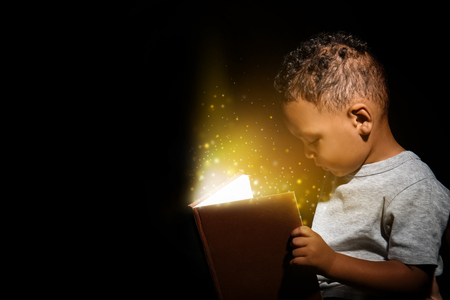 Little African-American boy reading magic book on dark background