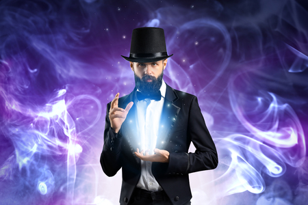 Male magician showing tricks in smoke Stock Photo