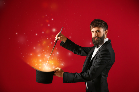 Male magician showing trick with hat on color background