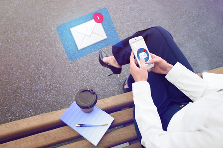 Young businesswoman with mobile phone checking an email outdoors
