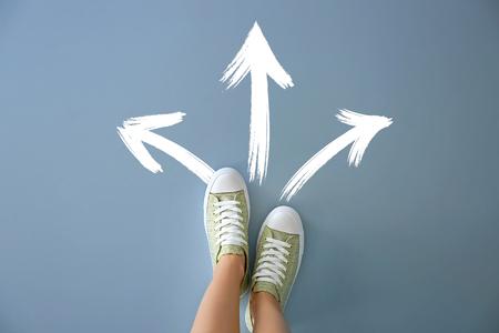Mujer de pie sobre fondo de color con flechas apuntando en diferentes direcciones. Concepto de elección Foto de archivo