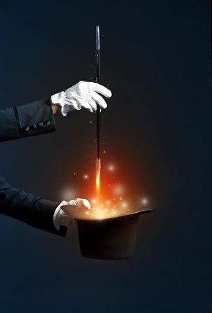 Magician showing trick with hat on dark background