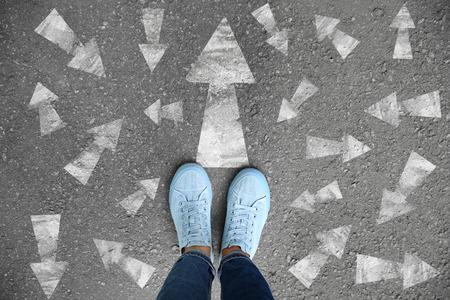 Donna in piedi su strada asfaltata con frecce che puntano in direzioni diverse. Concetto di scelta