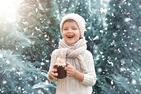 Cute little boy in warm sweater and with mason jar of hot chocolate on snowy day Foto de archivo