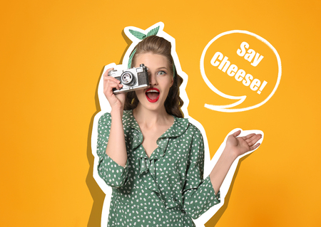 Beautiful young woman in pin-up style with photo camera on color background