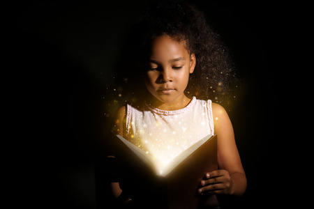 Little African-American girl reading magic book on dark background