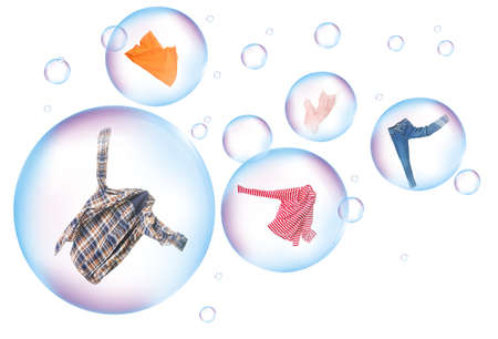 Soap bubbles with clean washed clothes on white background Foto de archivo