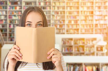Portrait of beautiful woman with book in modern library Foto de archivo