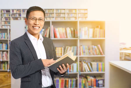 Handsome Asian man with book in modern library