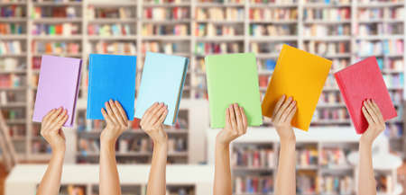 Female hands with books in modern library