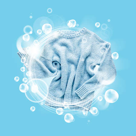 Clean sweater with soap bubbles on color background
