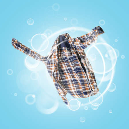 Clean shirt with soap bubbles on color background