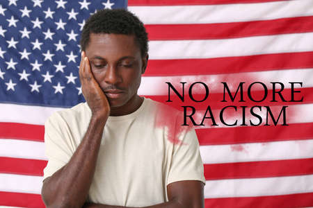 Sad African-American man near national flag of USA. Stop racism